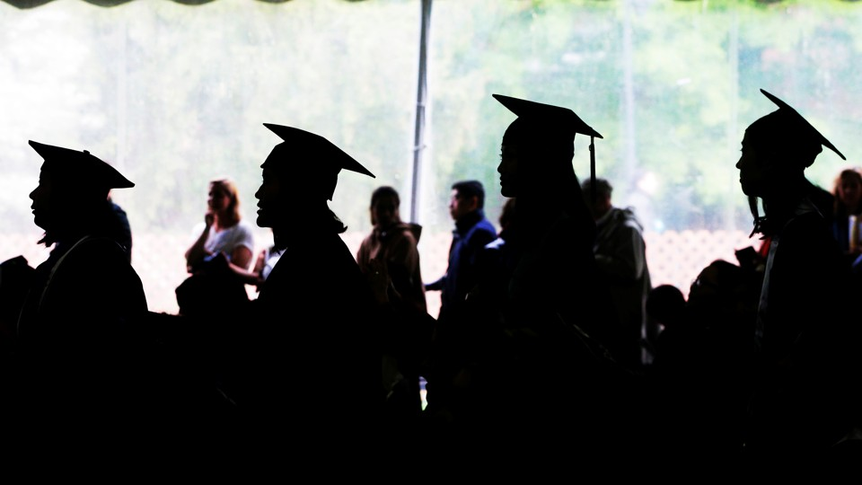 Female college graduates stand in a line.