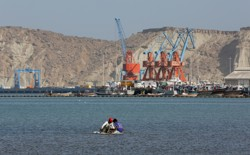 Boys sit on a piece of styrofoam sheet as they search for crabs in front of the Gwadar port in Pakistan.