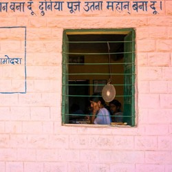 Students are seen studying through the window of a building.