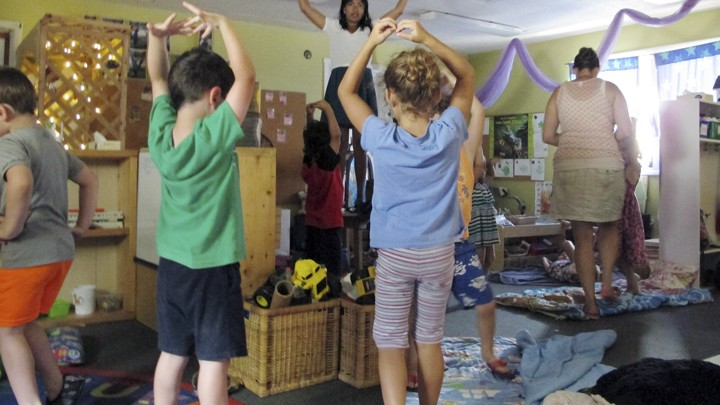 A teacher instructs preschool students in yoga.