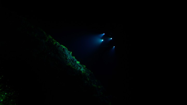 The lights of a submarine shine on a rock deep underwater.