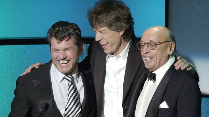 Jann Wenner, left, accepts his Rock and Roll Hall of Fame induction award from Mick Jagger and Atlantic Records founder Ahmet Ertegun 2004.