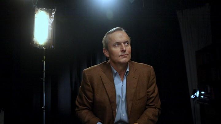 John Grisham sitting below stage lights