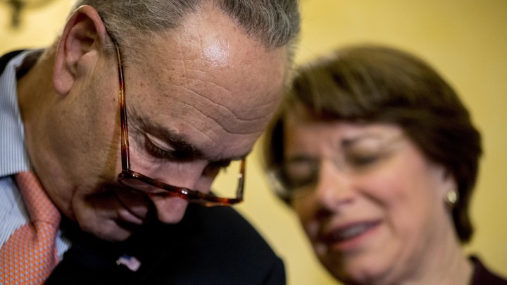 Senate Minority Leader Chuck Schumer and Senator Amy Klobuchar speak together during a news conference.