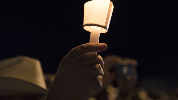 A hand holding a candle at a nighttime vigil