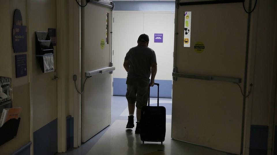 Man walking through hallway with suitcase