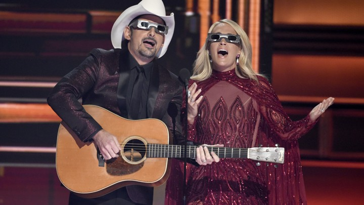 Co-hosts Brad Paisley and Carrie Underwood don eclipse glasses at the 2017 CMAs