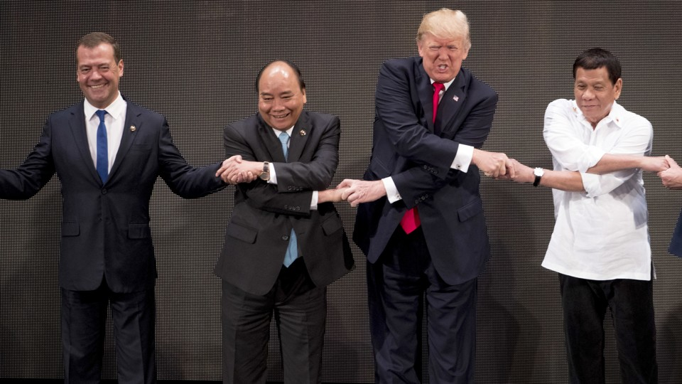 """President Trump takes part in the """"family photo"""" at the ASEAN summit."""