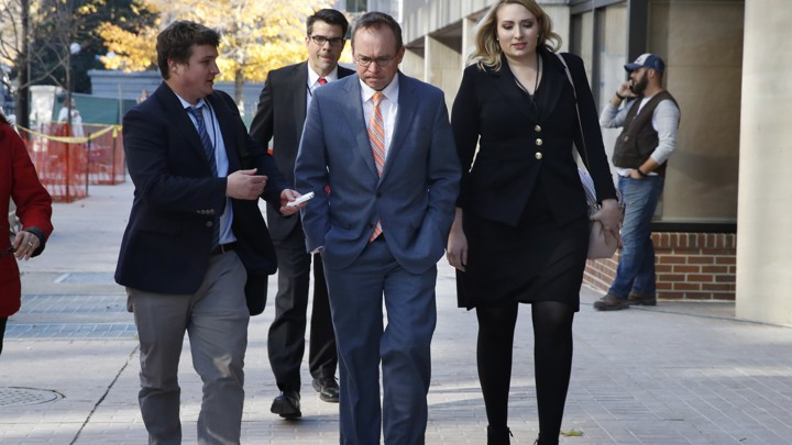 Mick Mulvaney (center) walks to the Consumer Financial Protection Bureau offices in Washington.