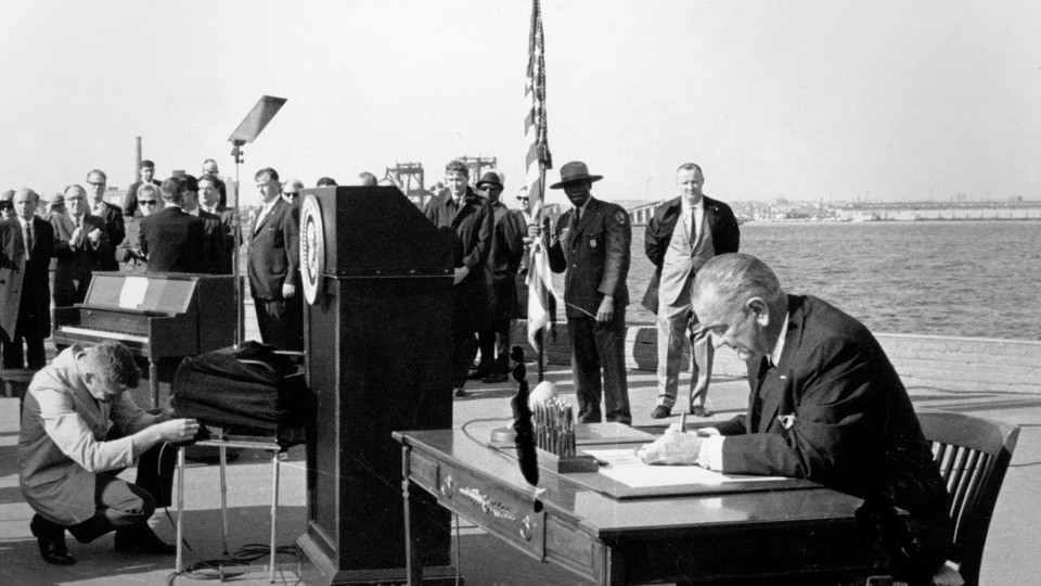 President Lyndon B. Johnson signs the new immigration bill on Liberty Island in New York Harbor.