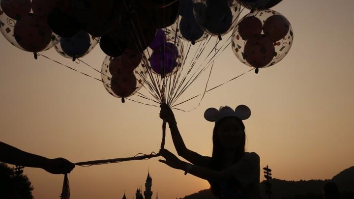 A woman holding balloons at the Hong Kong Disneyland