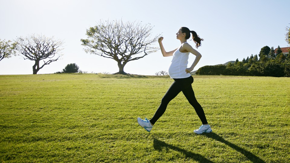 A pregnant woman exercising in a field