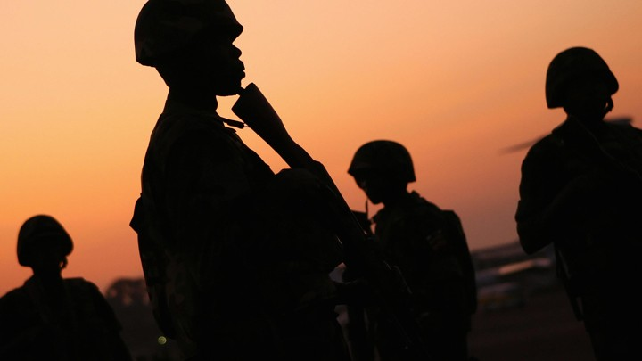 Ugandan soldiers of the African Union peacekeeping mission to Somalia stand before sunrise.