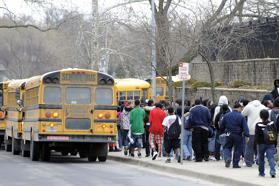 Students walk alongside school buses.
