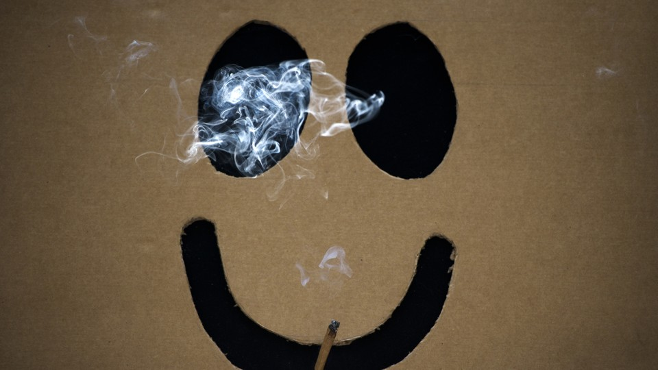 A smiley face smokes a joint of marijuana.