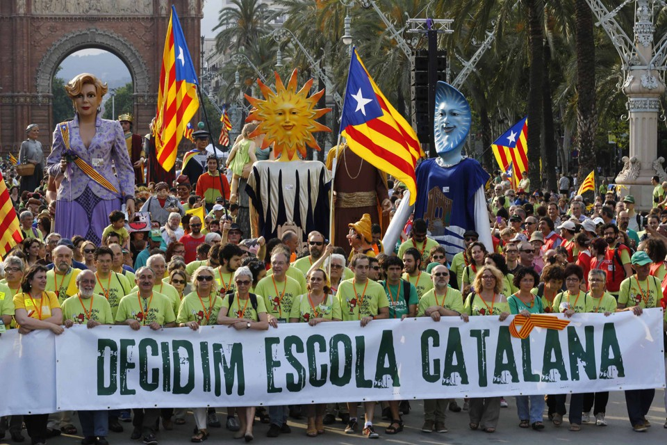 "Demonstrators carry a banner, which reads: ""Decided, Catalan school."""