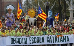 """Demonstrators carry a banner, which reads: """"Decided, Catalan school."""""""