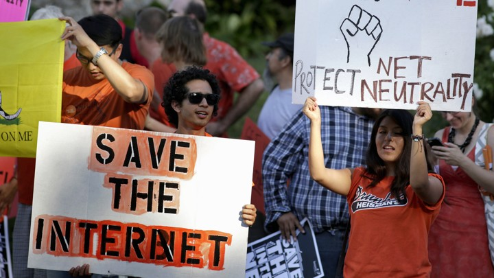 Activists hold signs at a rally for network neutrality.