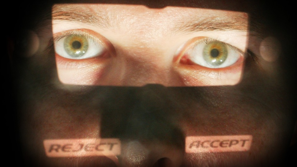 """A close-up of a man's face with the eyes illuminated and the words """"reject"""" and """"accept"""" superimposed on his cheeks"""