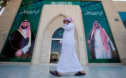 A man speaks on the phone as he walks past posters depicting Saudi Arabia's King Salman bin Abdulaziz Al Saud and Crown Prince Mohammed bin Salman.