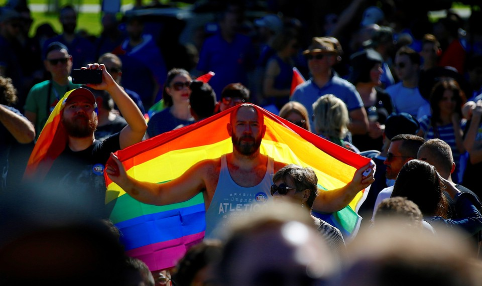 A 'Yes' campaign supporter holds a rainbow flag at a rally after it was announced that a majority of Australians support legalizing same-sex marriage at a rallyinSydney, Australia on November 15, 2017.