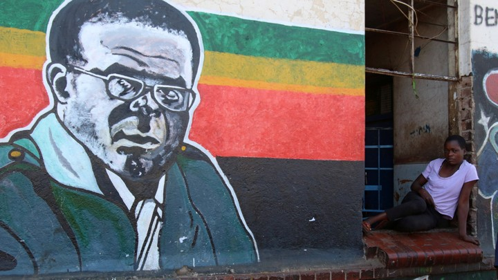 A woman sits next to a mural depicting Robert Mugabe.