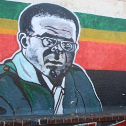 A woman sits next to a mural depicting Robert Mugabe.