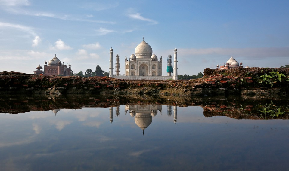 The Taj Mahal is reflected in a puddle.