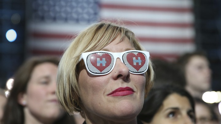 A woman wearing sunglasses with the Clinton campaign logo in front of an American flag