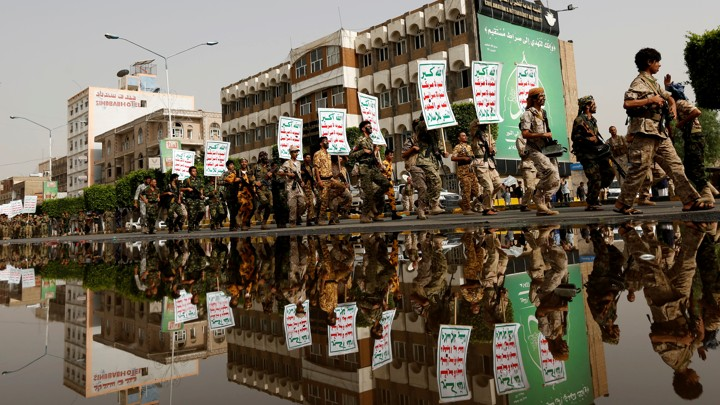 """Newly recruited fighters loyal to the Houthi rebels are reflected on a rain water pool as they march with placards reading: """"Allah is the greatest. Death to America, death to Israel, a curse on the Jews, victory to Islam""""."""
