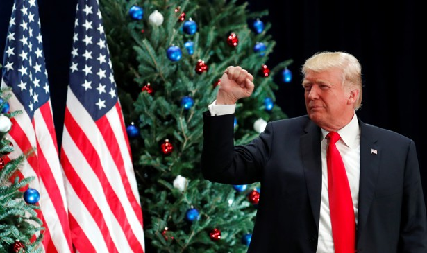 President Trump makes a fist while standing in front of American flags and Christmas trees.
