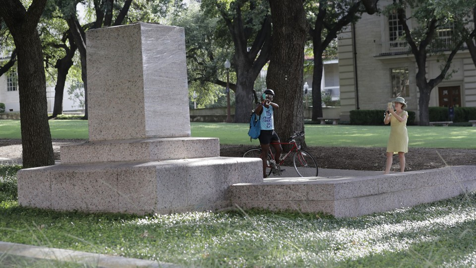 Two passersby take photos of a pedestal where a statue once stood.