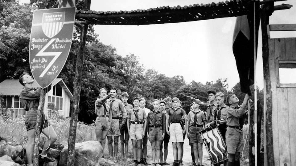 Nazi youths in uniform salute at the entrance to a German American Bund camp