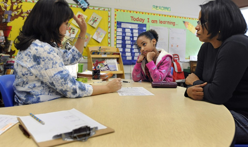 A parent, student, and teacher sit at a table.