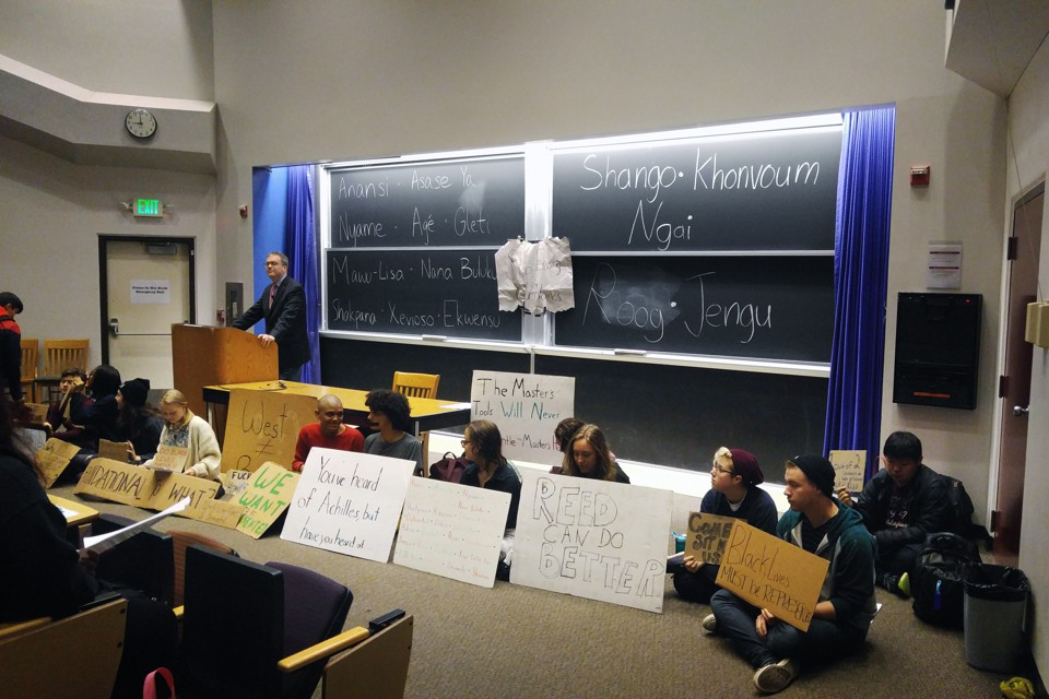 A professor stands at a lecture podium, while protesters sit alongside him holding signs.