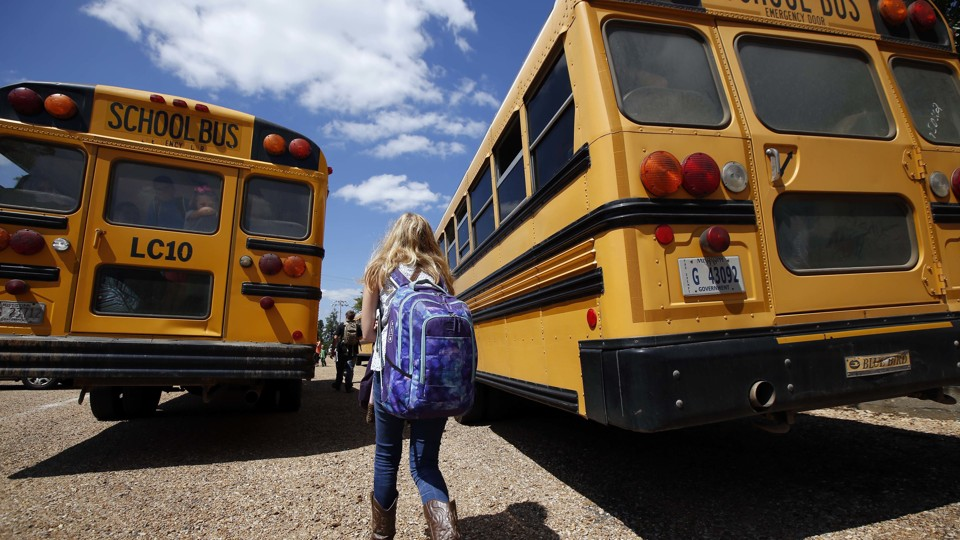 A girl walks toward two school buses.