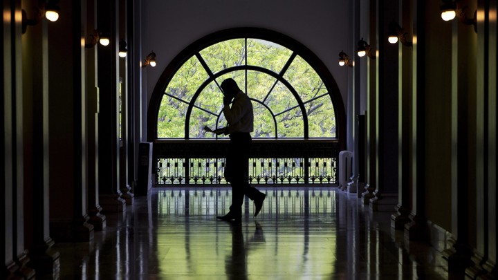 An unidentifiable man walks with a cellphone through a Capitol Hill building.