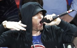 Eminem yells to the crowd before the start of an NBA basketball game between the Detroit Pistons and the Charlotte Hornets, Wednesday, Oct. 18,2017, in Detroit.