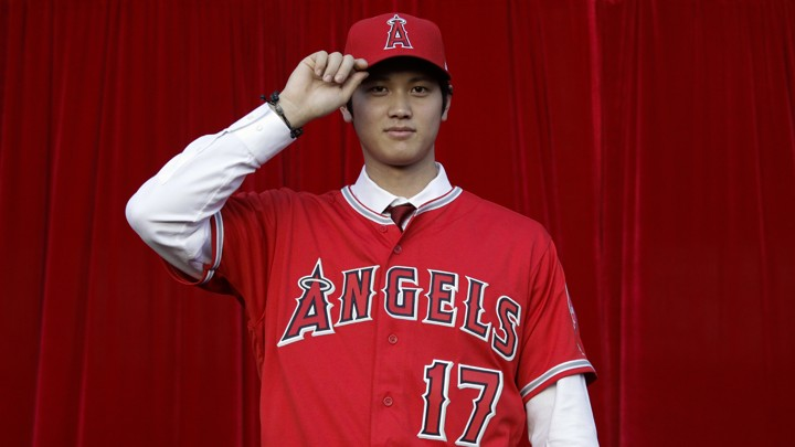 Baseball player Shohei Ohtani poses for photos after a news conference at Angel Stadium