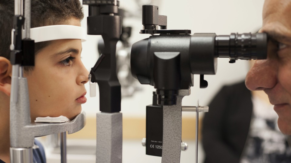 A young boy has his eyes examined by a doctor