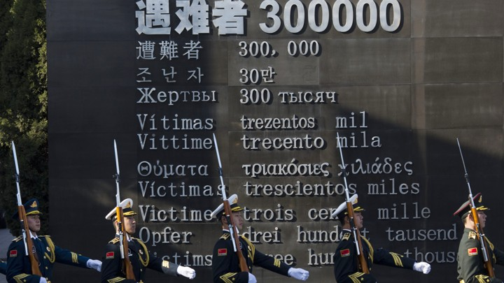 "Chinese honor guard members march past the words ""Victims 300000."""
