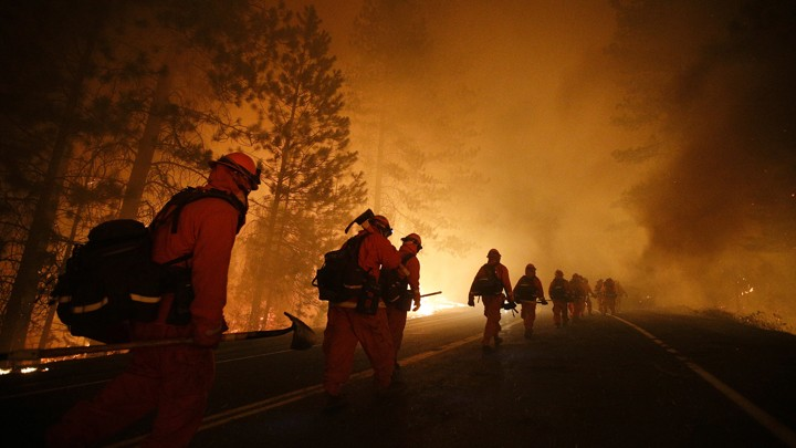A line of firefighters walks down a road as flames loom in the background.