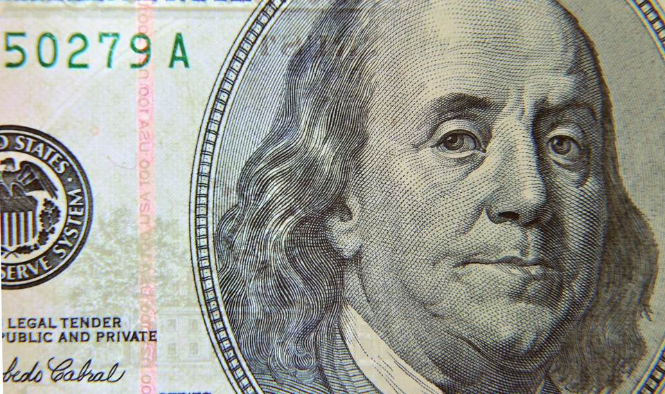 A close-up view of Benjamin Franklin's face on a $100 bill
