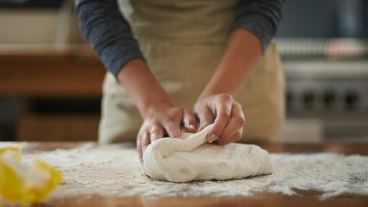 A woman kneads bread