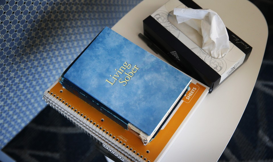 """A book titled """"Living Sober,"""" spiral notebooks, and a tissue box on a table"""