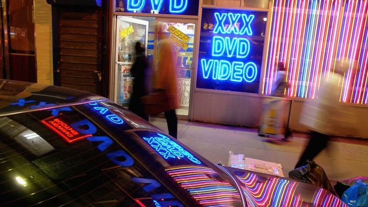 The neon lights of an adult-video store are reflected on a car.