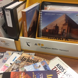 History and social studies textbooks sit on a desk.
