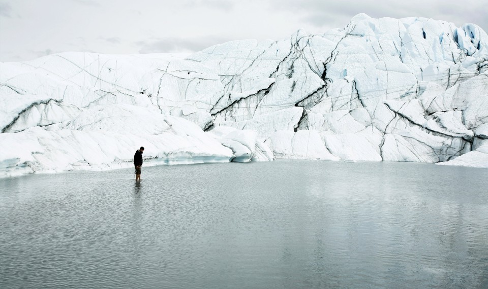 A person stands in water in front of a glacier.