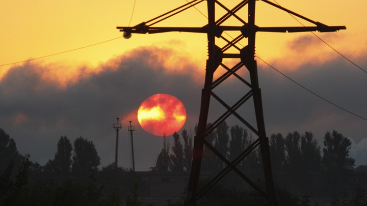 Power lines against a smoky red sky