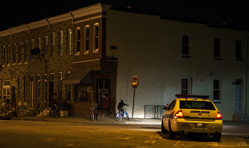 A police car sits on a street in East Baltimore, shining its headlights on a man riding a bike.
